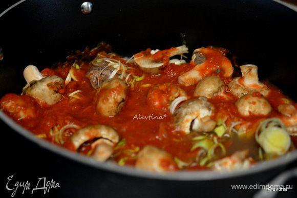Обжарить отдельно грибы на оливковом масле 1 ст. л. Лук-порей очистить и порезать тонко. Добавить в общее блюдо грибы, лук-порей, чеснок дольку, томаты баночные порезанные, зелень порубленную, соль и черный перец. Закрыть крышкой жаровню и поставить в духовку на 2-3 часа.