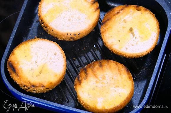 Разогреть в сковороде-гриль оставшееся оливковое масло, выложить булочки срезами вниз и обжаривать с двух сторон до появления золотистых полосок.