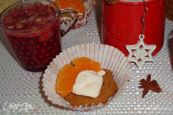 Пряничное печенье намазать сырным кремом и украсить очищенными от пленок дольками мандаринов.