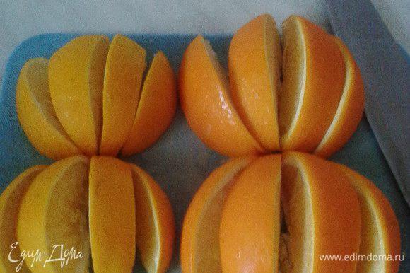 Затем замороженные апельсины полить тёплой водой, чтобы стали мягче и разрезать каждый на 8 частей.