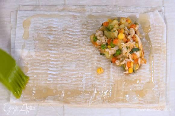 Каждый лист фило смазать оливковым маслом, сложить пополам, еще раз смазать маслом и сложить пополам, затем на уголок выложить начинку, промазать маслом края и накрыть свободным углом теста, чтобы получился треугольник.