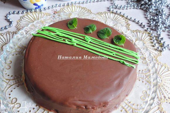 Для глазури растопим шоколад, смешаем с растительным маслом и тщательно перемешаем погружным блендером. На охлажденный торт из морозилки выливаем глазурь и даем ей самой растечься, можете немного ей помочь, наклоняя торт в нужную сторону. Я покрывала торт глазурью прямо на сервировочном блюде, хотя по правилам это следовало делать, поставив его на решетку, и лишь когда глазурь застынет, переложить его на блюдо. Для украшения в оригинальном рецепте на застывшей глазури следовало нарисовать полосы зеленым красителем и выложить листики мяты на шарики из крема. Я в отложенный заранее крем добавила зеленый краситель, нарисовала полосочки кремом и выложила свежие листики мяты.