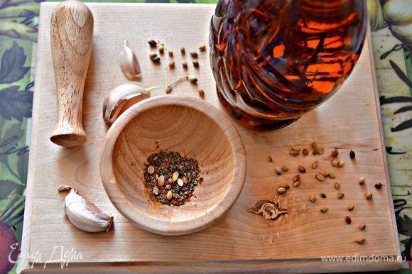 Чеснок очистите и разрежьте каждый зубчик вдоль на 3-4 ломтика. Специи соедините в ступке и разотрите. Переложите в небольшую ёмкость, добавьте оливковое масло и перемешайте.