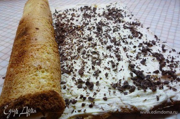 Остывший рулет разворачиваем, смазываем кремом и поверх крема посыпаем натертым на крупной терке горьким шоколадом. Часть крема оставляем для украшения.