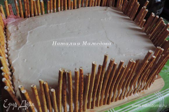 Далее я бока торта оформила соломкой, имитируя заборчик вокруг сказочного дворика. Мне понадобилось примерно 500 г соломки. Я каждую соломку обламывала до нужной длины, а ее остатки утилизировали дети.