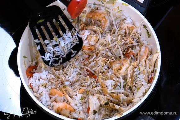 Добавить готовый рис, перемешать и немного обжарить, затем влить соевый соус, еще раз все перемешать.