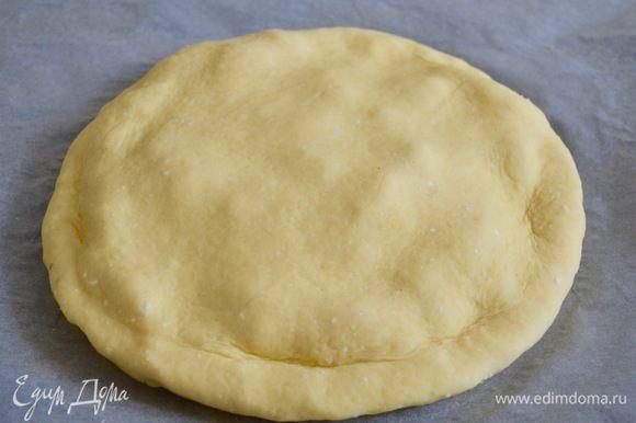 Вторую часть теста раскатать в лепешку чуть большего размера. Накрыть начинку второй лепешкой и подогнуть край под низ пирога.