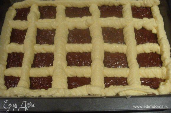 С помощью кондитерского мешка сделать сетку из крема на тесте.