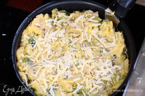 Дно сковороды, где жарился лук с грудинкой, посыпать половиной натертого сыра, выложить картофельно-капустную массу, разровнять ее и посыпать оставшимся сыром.