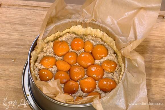 На подпеченный корж тонким слоем выложить марципановую массу, а затем половинки абрикосов срезом вниз.