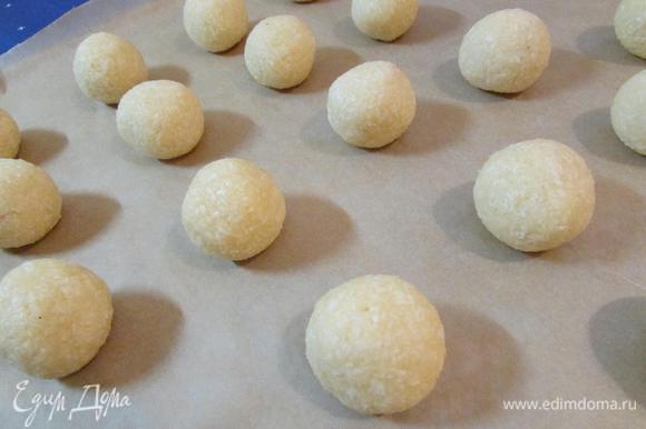 Можно формовать печеньки. Можно это делать влажными руками. У меня 26 кокосовых шарика, по 25 г. Выложить печенье на противень, застеленный пекарской бумагой.
