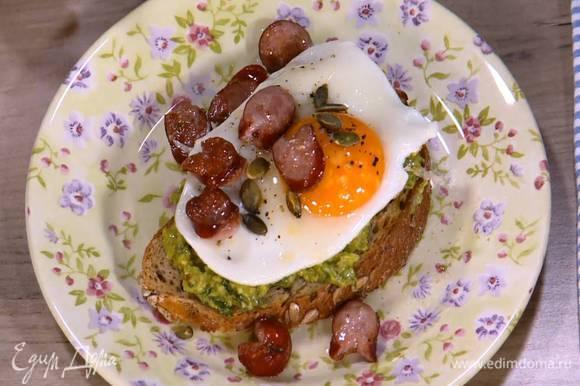 Подсушенный хлеб намазать массой из авокадо, сверху выложить глазунью, кусочки колбаски и посыпать все тыквенными семечками.