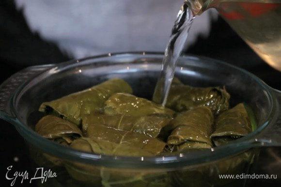 """Залить соком лимона, маслом и долить воду, чтобы она полностью покрывала рулетики. Далее есть два способа: 1. Готовить долму в духовке: для этого разогреть её на 205°С. Долму сложить в жаропрочную ёмкость, залить бульоном, накрыть крышкой и убрать на 1 час; 2. Готовить долму на плите: для этого сложить её в сковороду, залить""""бульоном"""", накрыть крышкой и поставить на средний огонь (4 уровень мощности, если плита электрическая) на 1 час."""