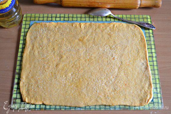 Раскатать тесто в прямоугольный пласт, смазать растительным маслом и посыпать сахаром (по 1 ст. л. с горкой на каждый пласт).