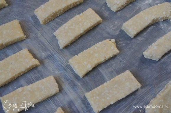 На присыпанном мукой столе, раскатать тесто в прямоугольник, толщиной около 1 см. Разрезать тесто на полоски. Уложить на смазанный маслом пергамент.