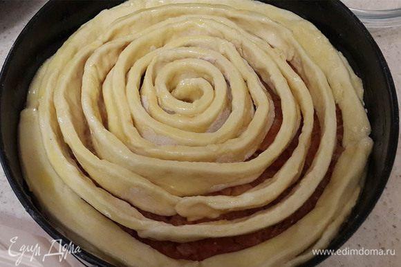 Выложить начинку. Украсить оставшимся тестом. Для этого раскатать тесто и нарезать на полоски. Скрутить, начиная от центра, по спирали. Смазать желтком с сахаром, взбитыми вилкой. Выпекать около 45-50 минут.