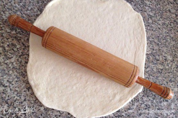 Раскатываем тесто (я люблю делать круглую форму). Чтобы тесто не прилипало к рабочей поверхности то лучше присыпать ее немного мукой (лишнее потом стряхнуть). Выложить на противень, накрыть кухонным полотенцем и дать настояться минут 15-30. Затем еще раз распределить его по противню (тесто немного могло приподняться пока настаивалось, поэтому для тех, кто любит тонкое тесто то его надо подраскатать еще немного. Включаем духовку на 180-200°С.