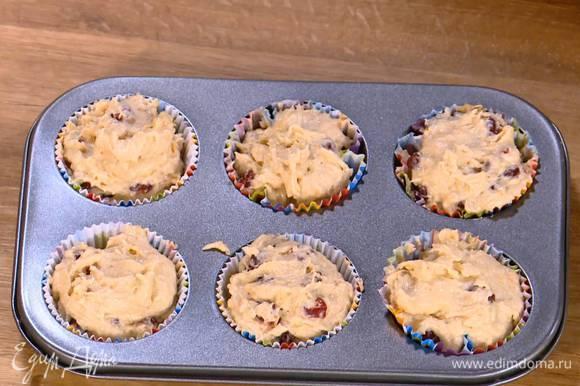 В формочки для кексов вставить бумажные вкладыши и разложить в них тесто.