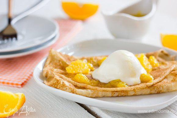 Готовые блины выложите на тарелку в центр положите фламбированные апельсины и сверните края блинов с двух сторон на начинку, сверху выложите шарик ванильного мороженого и полейте соусом.