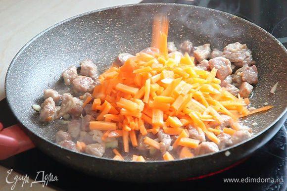 Открываем крышку, перемешиваем мясо с луком, доливаем растительное масло из нашего стаканчика и выкладываем нарезанную соломкой морковь.
