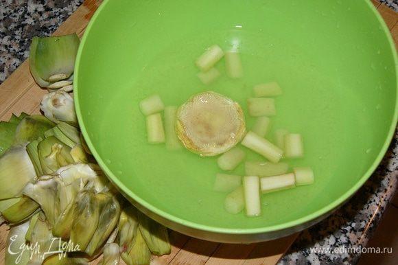 В емкость с водой, куда выдавлен сок половины лимона, немедленно опускаем нарезанный на брусочки стебель и очищенную сердцевину артишока. Артишок очень быстро темнеет.