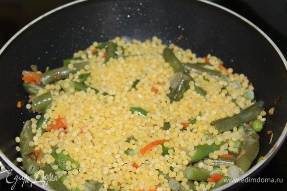 Затем добавить птитим. Обжарить его минут 7-10 вместе с овощами. Дальше готовим как ризотто, постепенно подливая бульон, доведите кускус до готовности.
