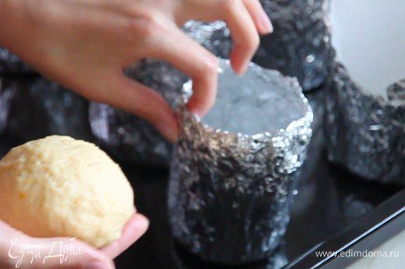 Выставляем на противень подготовленные формы и раскладываем в них тесто. Руками отделяем от теста шарики такого размера, чтоб они заняли 1/3 часть высоты формы. Края отделенного теста загибаем внутрь «шарика». Так верхушка кулича будет гладкой.