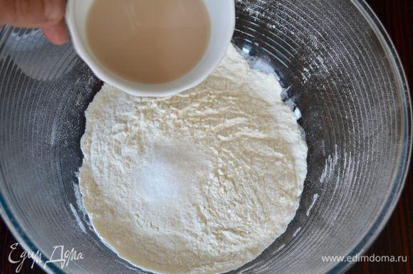 В миску просеять муку и добавить сахар. От общего количества теплой воды отлить 2 ст. л. и развести в ней дрожжи. Добавить сразу к муке и перемешать. Дрожжи можно использовать и сухие (3,6 г), тогда их просто добавить в муку.