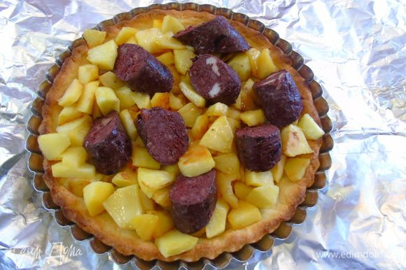На корж выкладываем яблоки, а сверху слегка утопив нарезанную кусочками колбасу.