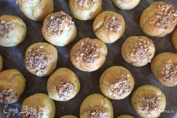 Немного крема намазываем на верхушки пирожных и макаем этими верхушками в дробленые орешки. Профитроли готовы!