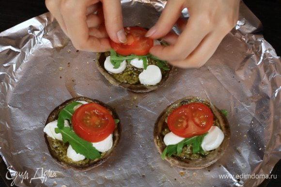 Смазать шляпки соусом песто, выложить помидоры, сыр, руколу.