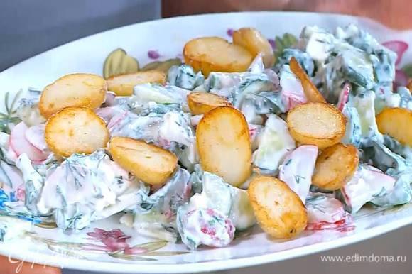 В огурцы с редисом добавить заправку, все перемешать и выложить на блюдо, сверху разложить обжаренный картофель.