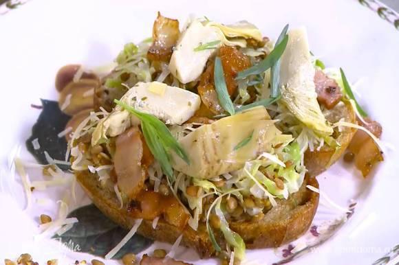 Выложить на тосты чечевицу с капустой, посыпать натертым сыром, сверху поместить кусочки сала и артишоки, украсить все листьями тархуна.