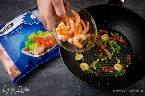 Разогреть в сковороде кунжутное и оливковое масло и обжарить зеленый лук и чили. Чеснок почистить, раздавить ножом и добавить в сковороду. Имбирь почистить, натереть на мелкой терке (должно получиться 1/2 ч. ложки), отправить в сковороду с луком и чесноком, все перемешать. Добавить креветки и обжарить их вместе с овощами почти до готовности.