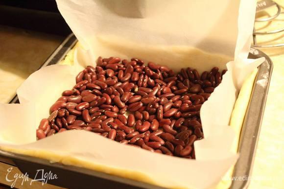 Внутрь на пекарскую бумагу выложить фасоль и отправить в разогретую до 180°С духовку на 15 минут.