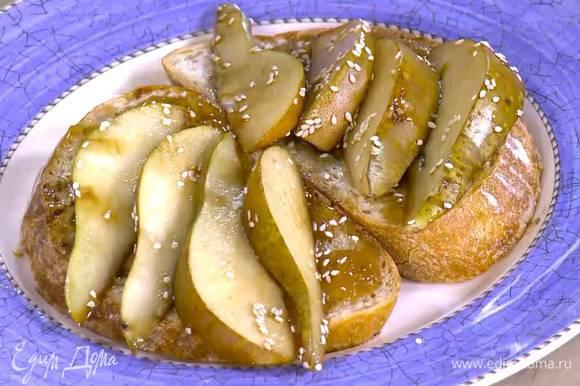 Сверху смазать тосты инжирным вареньем, посыпать оставшимся кунжутом, разложить ломтики груш и нарезанный сыр.