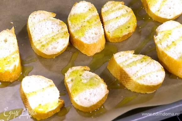 Кусочки хлеба выложить на противень, выстеленный бумагой для выпечки, сбрызнуть 1‒2 ст. ложками оливкового масла Extra Virgin и отправить под разогретый гриль на 1‒2 минуты.
