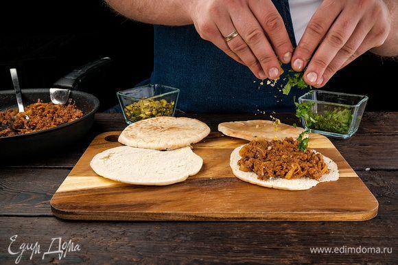 Готовые лепешки выложить на противень, сверху добавить мясную начинку. Разложить зелень и фисташки.