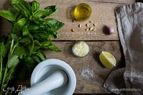 Базилик промойте и тщательно просушите. В чашу блендера сложите листья базилика, кедровые орешки, чеснок и сок лимона, измельчите до получения однородной массы.