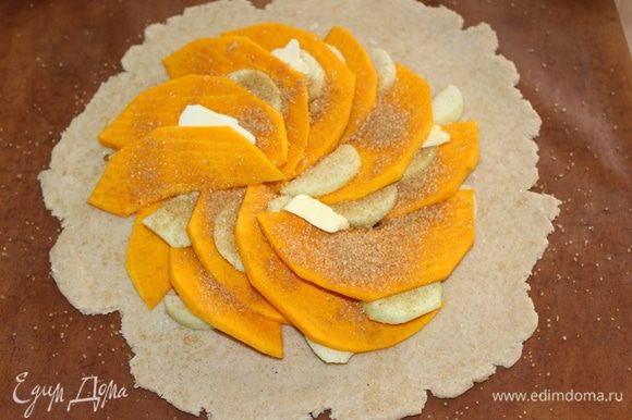 Тесто раскатать, выложить на него тыкву, нарезанную тонкими пластинками, дольки яблока, кусочки сливочного масла. Посыпать сахаром.