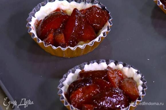 Смазать тесто в формочках предварительно размягченным сливочным маслом, присыпать оставшимся сахаром и разложить сливы со специями.