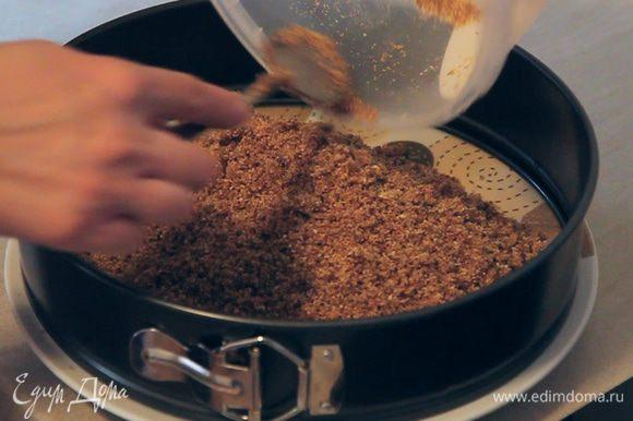 Полученную смесь пересыпаем в разъемную форму, установленную на тарелку. Формируем слой толщиной 1,5 — 2 см, хорошо приминая все ложкой. Верхняя поверхность слоя должна получиться максимально ровной. Ставим форму в холодильник.