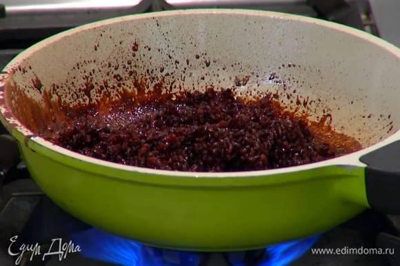 В сковороду с оставшимся от вишни соусом выложить отваренный рис, перемешать и прогревать 1‒2 минуты.