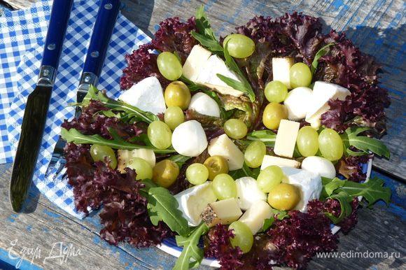 Листья салата выложить на тарелки, добавить руколу. Сыр нарезать брусками, бри — дольками. Выложить сверху салата, добавить моцареллу, виноград, орехи и оливки.