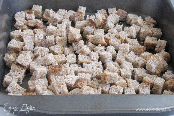 Цельнозерновой хлеб порезать небольшими кубиками и подсушить в духовке 7 — 10 минут при температуре 180°С.