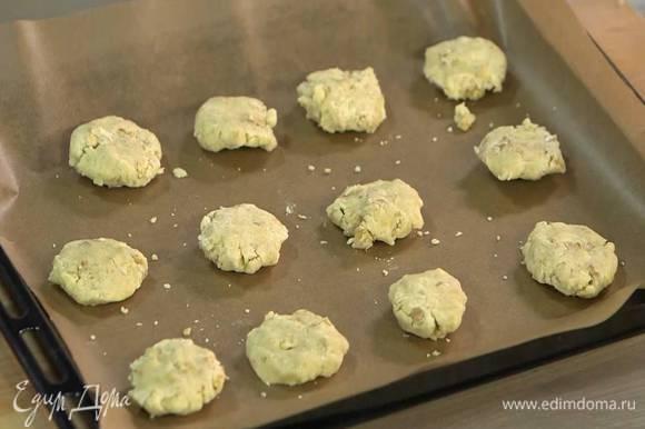 Руками сформировать из теста небольшие, плотные лепешки и выложить на противень, выстеленный бумагой для выпечки.