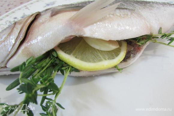 В брюшко каждой рыбы положить травки, по пластинке чеснока и лимона.