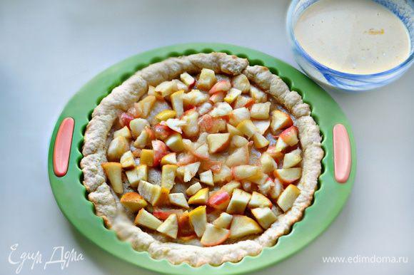 Разложите тушеные яблоки по поверхности теста, присыпьте сверху изюмом.