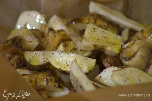 Небольшой глубокий противень выстелить бумагой для выпечки, выложить топинамбур, посолить, поперчить, сбрызнуть оливковым маслом, перемешать и запечь в разогретой духовке.