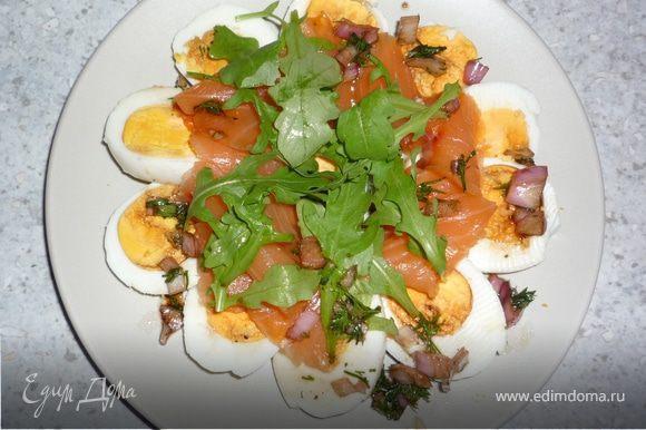 Листья руколы помыть и высушить, немного нащипать. Семгу нарезать небольшими полосками. Яйца нарезать кружочками. На тарелку выложить яйца в форме круга, сверху кусочки семги и руколы. Полить соусом. Приятного аппетита!
